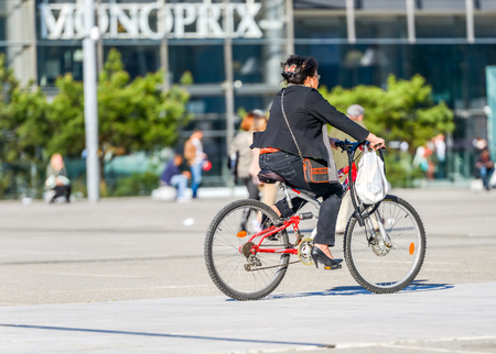 La defense, France - April 09, 2014: woman ride a bike in town. Alternative ecological clean transport in a city