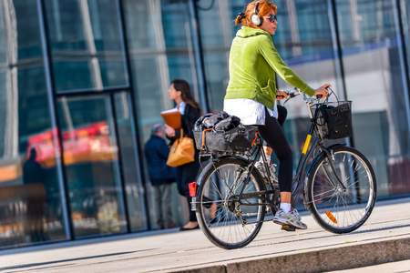 La defense, France - April 10, 2014: woman cycling by listening to music with headphones in town. Alternative ecological clean transport in a city Editorial