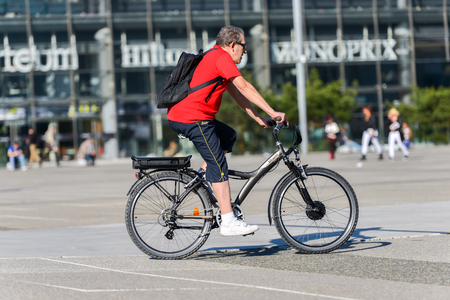 La defense, France - April 09, 2014: Man ride a bike in town. Alternative ecological clean transport in a city