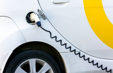 plugged in: Electric Car Being Charged. Charging an electric car with the power supply plugged in.