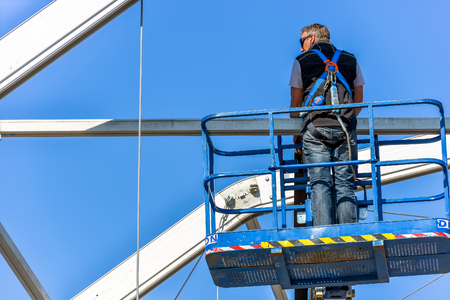 La defense, France- April 10, 2014: worker attaching fasteners to a beam at the top of a nacelle with blue sky on background Editorial