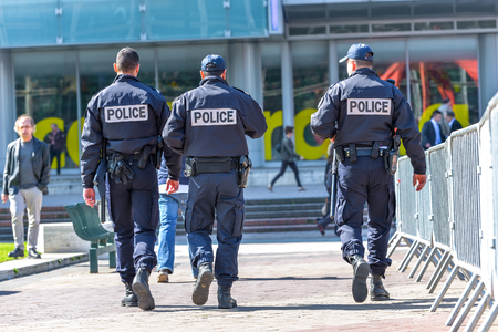 La defense, France- April 10, 2014: Back view of tree police officers walking in the center of La defense, great business block near Paris. 報道画像