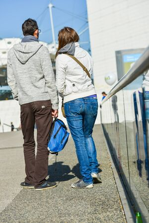stilish: La defense, France- April 10, 2014: young couple walking in a street.The girl is wearing blue jeans and the man brown pant Editorial
