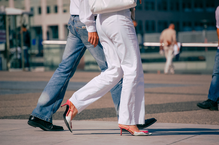 stilish: La defense, France - August 30, 2006:Stylish couple walking in a street. The man is wearing blue jeans and the woman white pant and pretty shoes feet