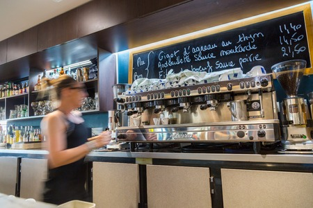 La defense, France - July 17, 2016: blurry barmaid in big traditional french restaurant in la defense city, the greatest business center in france near Paris.