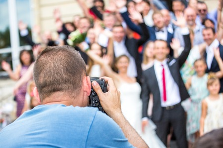 Wedding photographer in action, taking a picture of group of guests Stock Photo