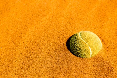Tennis ball inserted into the sand. Concept, Metaphor