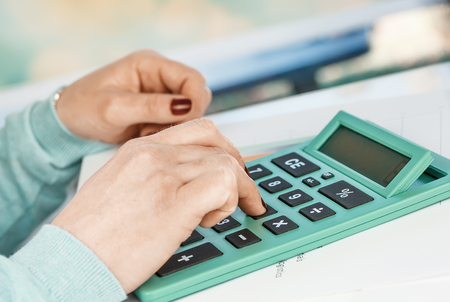Close-up portrait of red nails businesswoman hand while using calculator.