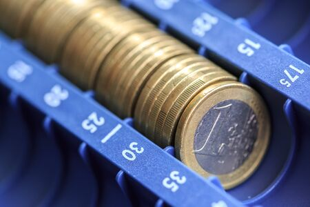 tax aligned: Open cash registrer containing many coins of euros in raw Stock Photo