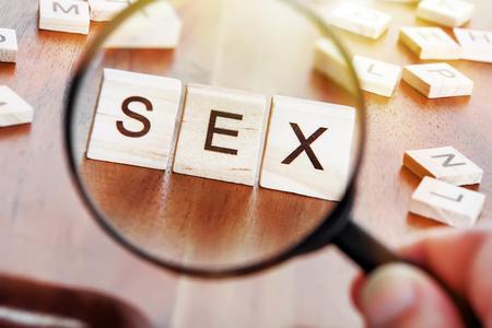 imagen del concepto de una lupa zoom sobre una palabra SEXO colocado sobre un escritorio en madera preciosa