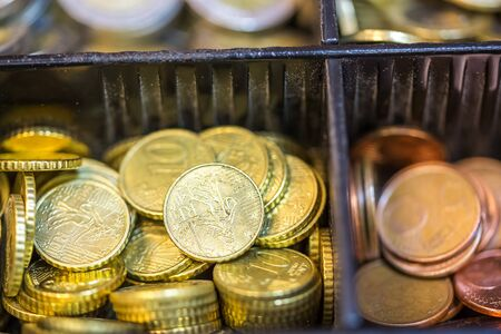 tax aligned: Open cash registrer containing many coins of euro ans banknotes