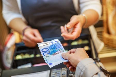 女性はユーロ紙幣を現金で支払う 写真素材