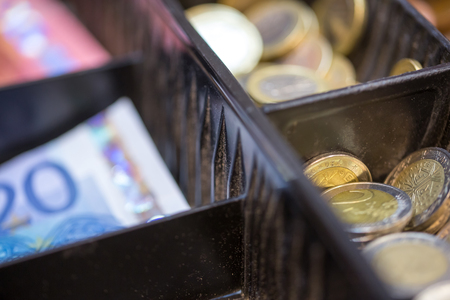 tax aligned: Open cash register containing many coins of euro and banknotes