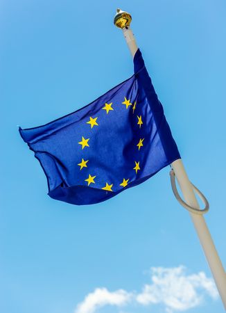 flag of the European Union with clouds underneath symbolizing darkening
