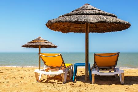 sunshades: Beach umbrellas and deckchair on the tropical beach