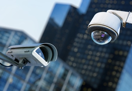 twee cctv beveiligingscamera's in een stad met blury zakelijke voortbouwend op achtergrond