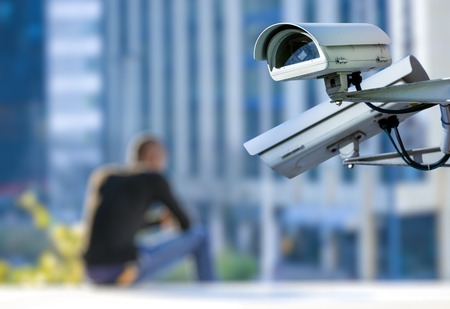 security CCTV camera or surveillance system with young man on blurry background Stock Photo