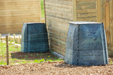 nourishing: Black plastic compost bin and small wooden cabin in town garden