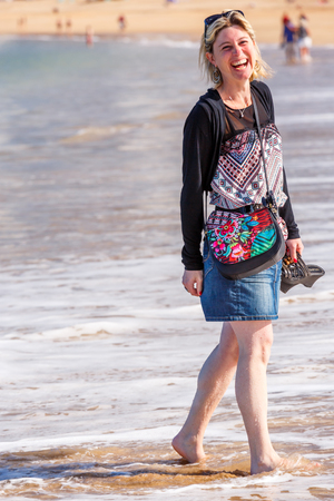 Saint-Jean de Luze, France - Sept 28, 2016: Joyful portrait of a smiling young woman, feet in the water on a beach in the Atlantic Ocean. She wears a city outfit, a skirt, a handbag and her shoes in her hand Editorial