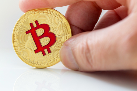 Golden bitcoins (virtual coins) in a hand on white background