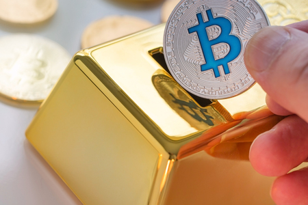 Concept of Cryptocurrency physical bitcoin with gold bullion piggy bank
