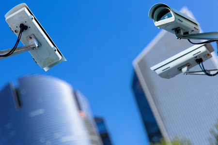 two cctv security camera in a city with blury business building on background