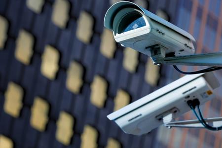 cctv beveiligingscamera in een stad met blury business gebouw op de achtergrond
