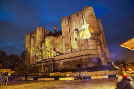 Niort, France - December 05, 2017: Illuminations of Christmas and light projection on the face of the dungeon on the main square of downtown niort