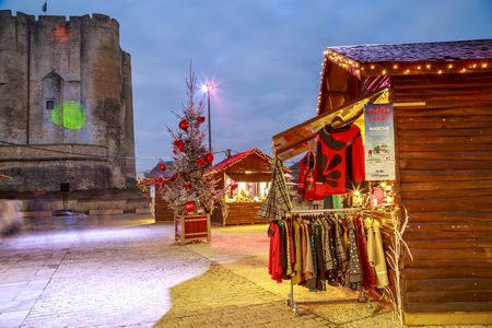 Niort, France - December 05, 2017: craftsmans cottages with illuminations of Christmas and light projection on the face of the dungeon in the background