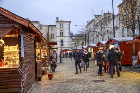 Niort, France - December 03, 2017: Christmas market at night during the festive period vendors sell from temporary wooden chalets in the city centre of Niort town.