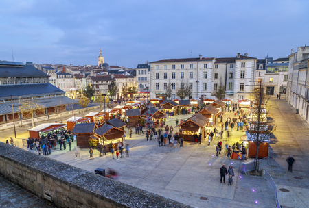 Niort, France - December 03, 2017: Panoramic view of christmas market at night during the festive period vendors sell from temporary wooden chalets in the city centre of Niort town. Editorial