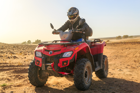 Ait Saoun, Morocco - February 22, 2016: Man riding RZR 800 in Ait Saoun dessert in Morocco on a sunset evening.