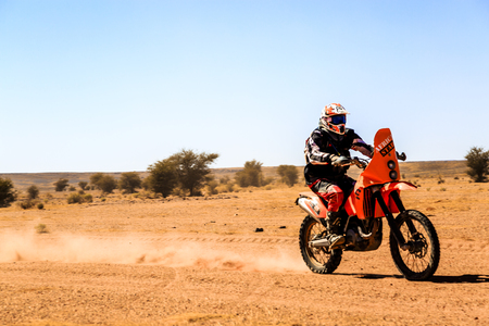 Ait Saoun, Morocco - February 23, 2016: Man riding quad bike in Ait Saoun desert in Morocco against the blue sky.