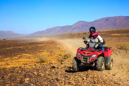 Ait Saoun, Morocco - February 22, 2016: Man riding atv quad bike on sand in desert on a sunny day in Ait Saoun desert in Morocco. Editorial