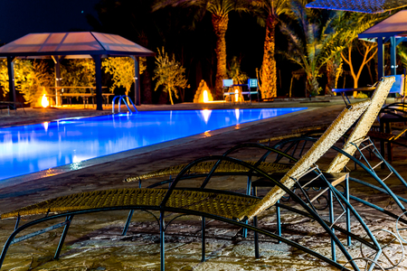 Mhamid, Morocco - February 22, 2016: Swimming-pool in resort with around deck-chairs for relaxing in blue sea water night scene. MHamid El Ghizlane is a small oasis town in southern Morocco. Editorial