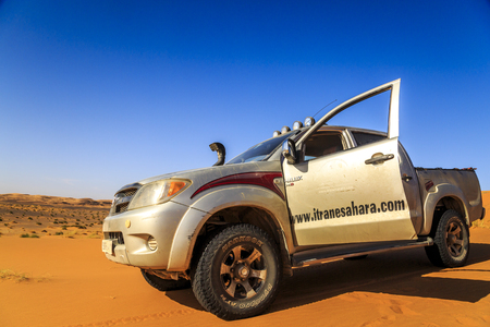 Merzouga, Morocco - February 25, 2016: Silver Toyota Hilux car with open front door and view to the desert. Merzouga is famous for its dunes, the highest in Morocco.