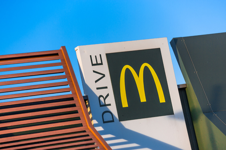 Beaulieu, France - October 26, 2015: McDonalds yellow and red drive-thru logo advertising sign placed on white board against clear sky. McDonalds Corporation is a fast-paced American fast-food chain founded by businessman Ray Kroc in 1952.