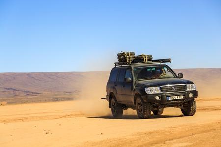 Ait Saoun, Morocco - February 22, 2016: Man driving toyota land cruiser in Ait Saoun desert of Morocco on a bright sunny day. 新闻类图片