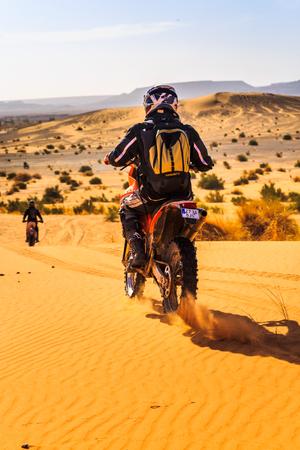 Ait Saoun, Morocco - February 25, 2016: back vue of man in helmet riding bike in Ait Saoun desert of Morocco