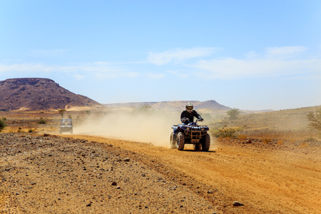 Young man in bike dress and helmet riding quad bike in desert