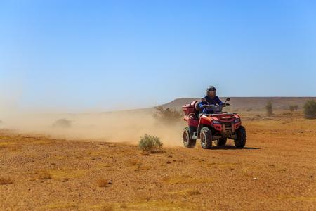 Man enjoying atv quad ride bike in desert on a bright sunny day