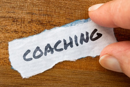 The word Coaching concept and theme written on old paper on a grunge background 스톡 콘텐츠