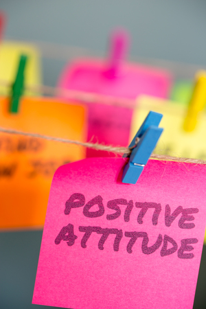 A set of colorful sticky notes with positive affirmation words and phrases featuring Positive Attitude on a bright pink sticky note hung from a clothesline by a blue clothespin.