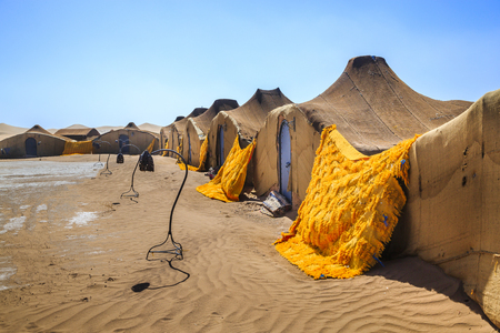 Nomadic settlement in the Sahara Desert .The structures all have blue doors and are made from woven cloth. Stock Photo