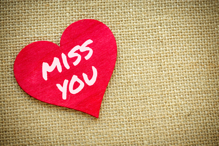 Closeup on Heart with Miss you word isolated on a burlap fabric. Valentines Day and love concept Stockfoto