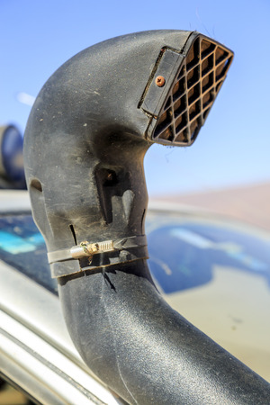 Close-up of black car truck exhaust pipe against clear blue sky