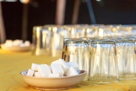 closeup on Two plates containing sugar cubes and several upside down glasses on a table