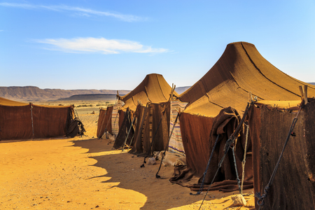 Nomad tents in the middle of the desert with mountains in the background on a sunny day