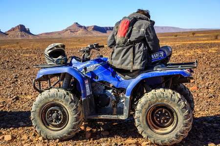 Merzouga, Morocco - February 22 2016: a man sitting down on a quad with his helmet next to him in the middle of the Moroccan desert, with mountains in the background.