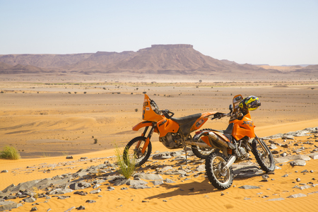 Merzouga, Morocco - February 26 2016: two orange motobikes in the middle of the sandy and rocky Moroccan desert with a set of mountains in the background, on a sunny day